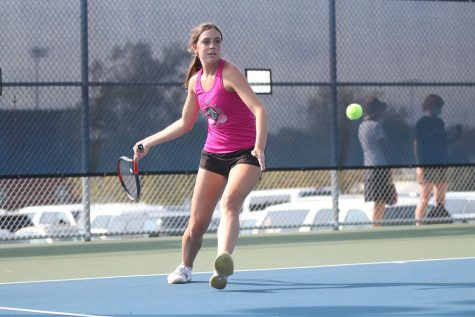 With her eyes on the ball, senior Sophie Lecuru steps forward with her racket to hit the ball at tennis regionals Saturday, Oct. 10. The girls tennis team placed third overall and Lecuru is advancing to play at state.