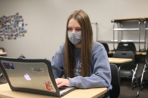 Sitting in an empty classroom, freshman Abby Wolff works on her canvas assignment on Monday, Oct. 19.