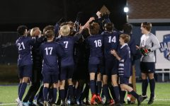 Regional championship award in the air, the boys soccer team celebrates their victory together.