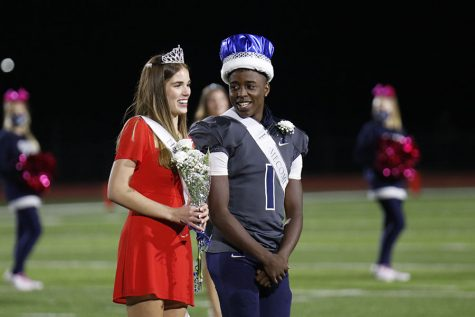 Posing for the cameras, homecoming king Quin Wittenauer smiles at homecoming queen Ellie Boone.