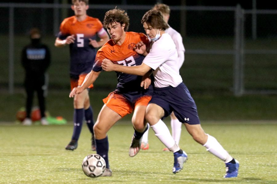 With an opponent at his side, junior Ryan Wingerd attempts to gain possession of the ball during the game against Olathe East Friday, Oct. 2. The Jaguars trailed Olathe East 2-0.