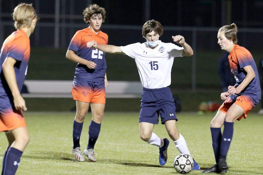 With three opponents surrounding him, junior Ryan Wingerd maneuvers the ball toward his teammates.