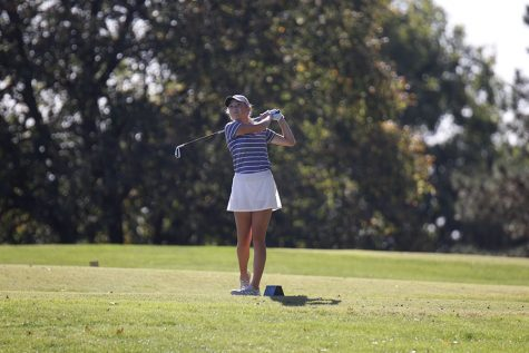 Watching the ball, junior Charley Strahm follows through on her swing.