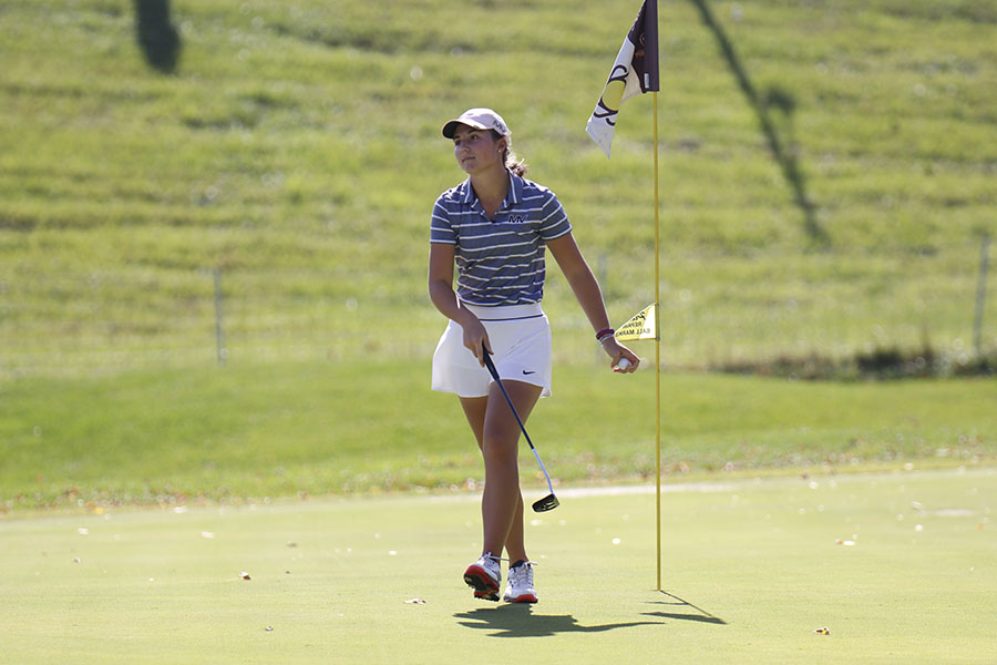 After retrieving her ball, junior Libby Green walks back to her clubs.