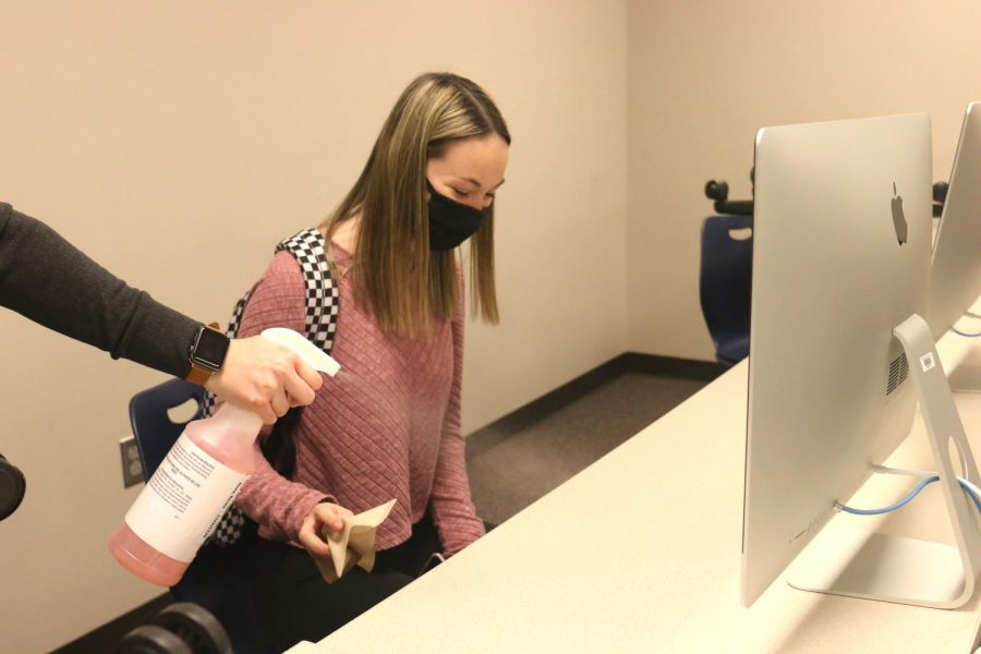 Before leaving class, senior Ella Greenup wipes down her desk with a paper towel and disinfectant Thursday, Oct 1.