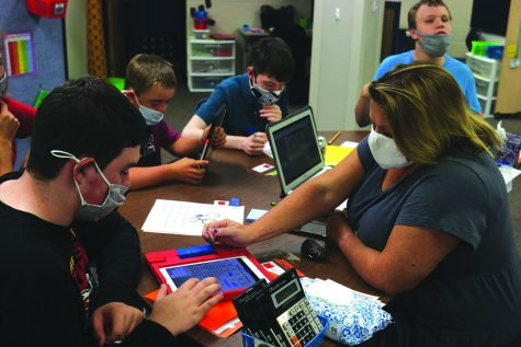 While gathered around the table, special education teacher Sara Evans helps junior Gabe Fuller complete an activity on an iPad during her daily living class Monday, Sept. 28.