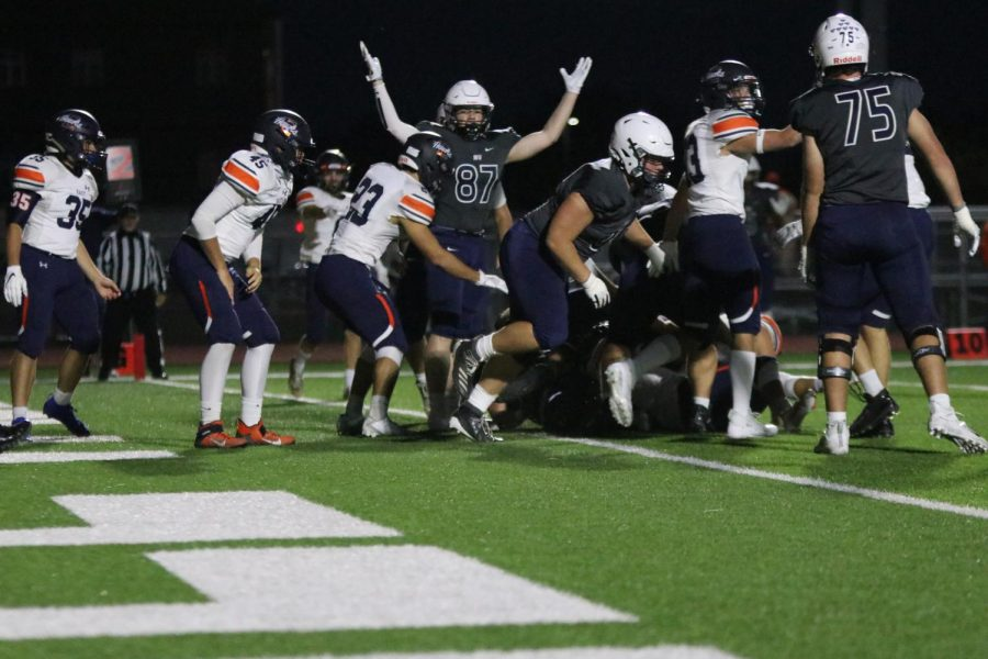 Hands in air to represent a touchdown, wide receiver Jared Napoli stands next to the pile of football players to show the referee that they had made it into the end zone.