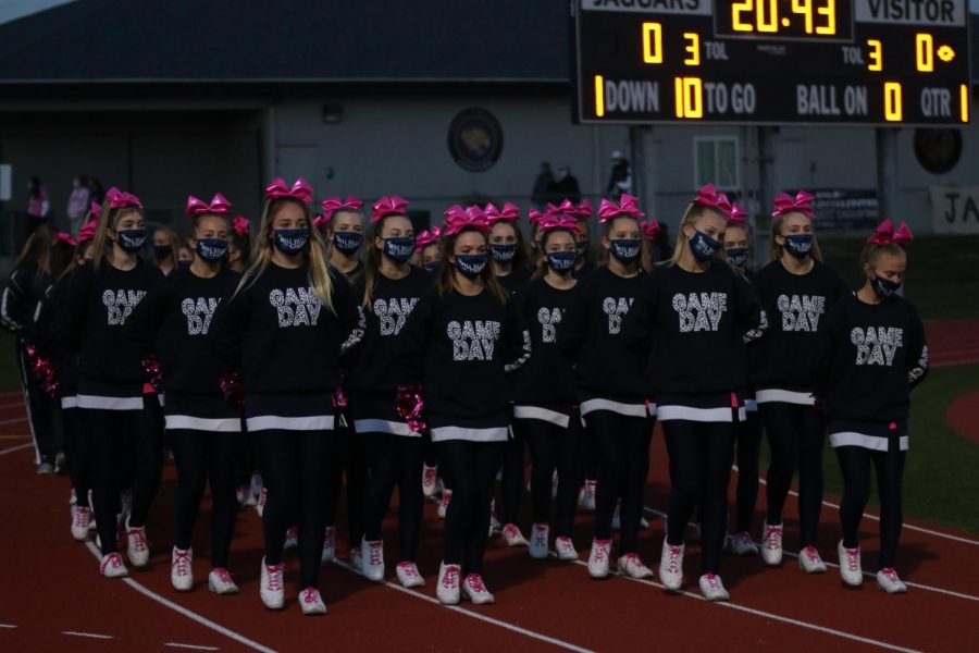 With hands behind their back, the cheerleaders walk down the track to get ready to cheer for the game.
