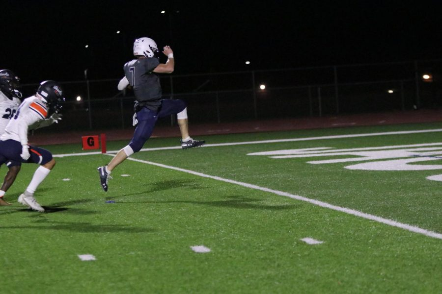 While scoring a touchdown, quarterback Cooper Marsh jumps into the air.