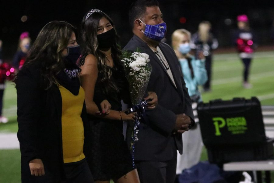 As she walks with her arms interlocked with her parents, senior Isabella Loya smiles while walking to meet up with her partner.