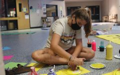 Sitting on the floor, freshmen Lauren Prestia paints a plate yellow. StuCo and volunteer students got together to decorate the school in class colors for Homecoming week on Sunday Oct. 11.