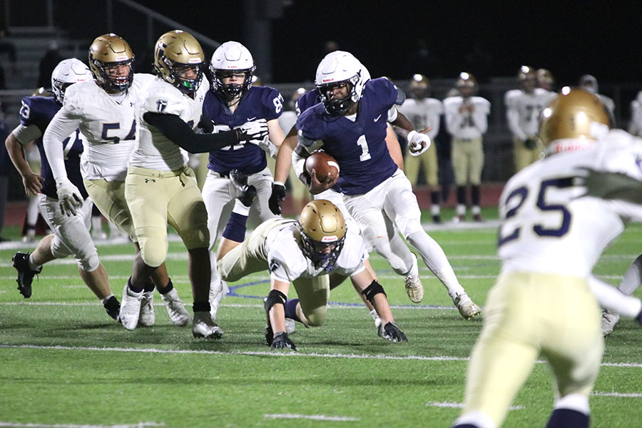 To dodge being tackled, running back Quin Wittenauer carries the ball between an opening in the middle of the field to run the ball towards the end zone.