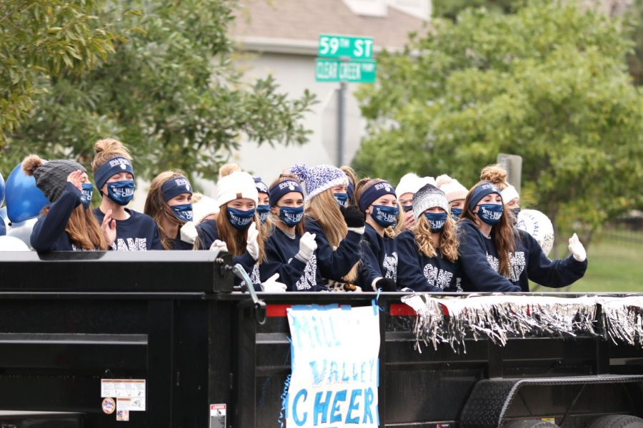 The school cheerleaders wave to a crowd of on-lookers in Clear Creek during the senior organized homecoming parade on Sunday, Oct. 18.