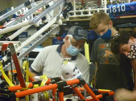 Lead robotics mentor Gary Hannah explain the teams robot to De Soto freshman Moses Morton. Thursday, Nov. 19