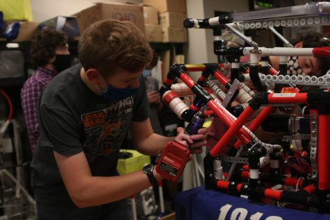De Soto freshman and new robotics recruit  Moses Morton uses a drill on last years robot, the Red Skeleton Thursday, Nov. 19