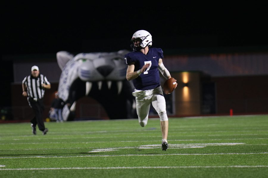Running down the sideline, quarterback Cooper Marsh looks for someone to throw to.