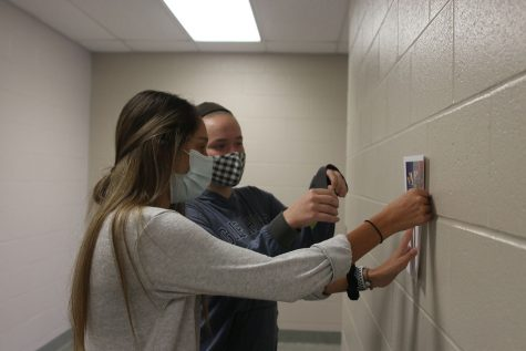 Taping a poster to the wall, juniors Carly Knight and Vania Arora kick off French week Wednesday, Nov. 3.