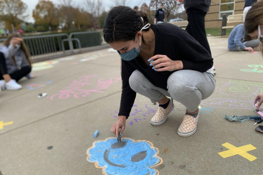 Bent down with a piece of black chalk in her hands, senior Nicole Crist draws a happy cloud at Prairie Ridge Elementary, Wednesday, Nov. 4, to bring positivity to the elementary students for the end of the quarter with several other members of the National Honor Society.