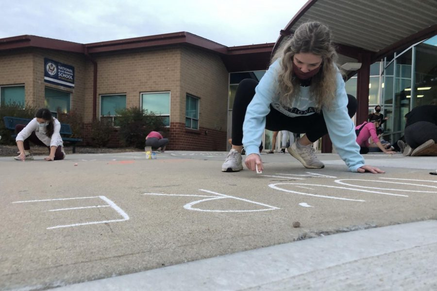 Crouched over her art, senior Tyler Bret draws with chalk at Clear Creek Elementary for NHS hours.
