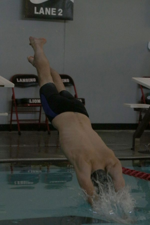 Mid-air, junior Brendan Akehurst dives off the block as the first swimmer of his relay Saturday, Dec. 5.