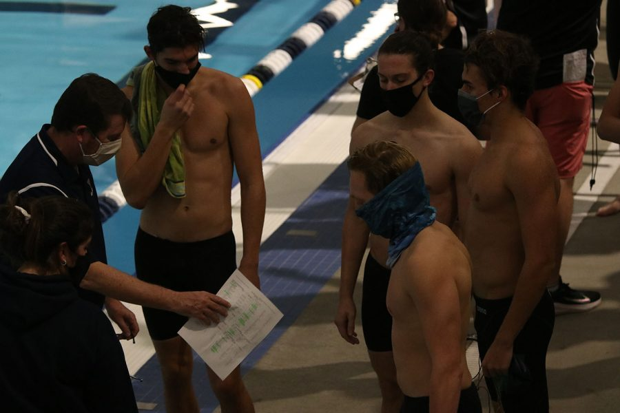 Speaking to the relay after their 200-yard freestyle relay, head coach Dan Dervin talks strategy with the boys.