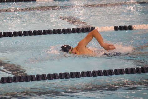 Slicing through the water, senior Cole McClure swims against his competitors in the 500-yard freestyle.