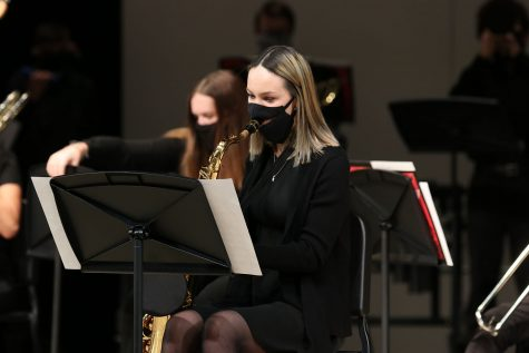 Eyes on her music, senior Ella Greenup continues playing her saxophone. The jazz band live streamed their first performance from the performing arts center over YouTube Wednesday, Dec. 9.