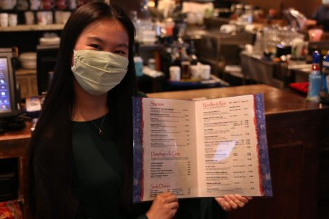 Inside of her family restaurant, sophmore Sophia Chang displays the menu for Blue Koi which consists of a variety of different Asian comfort foods.