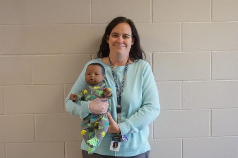Teaching the class how to take care of their fake babies, Human Growth and Development teacher Ellen Gray shows off her baby via zoom on Dec. 4.