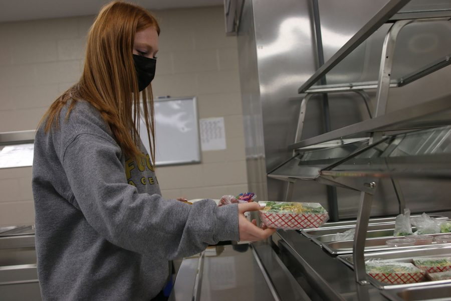 This year for lunch, salads are premade and sealed as part of newly implemented safety measures, which junior Lauren Butler places onto her tray Monday, Nov. 16.
