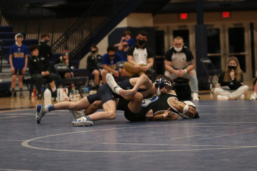 Leaning down on his opponent, freshman Dillon Cooper attempts to push his shoulders down.