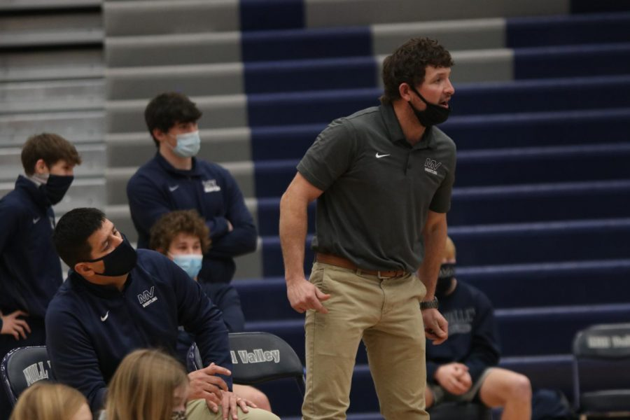 At the corner of the mat head coach Travis Keal and assistant coach Jake Ellis yell to freshman Dillon Cooper as he faces off against his opponent.