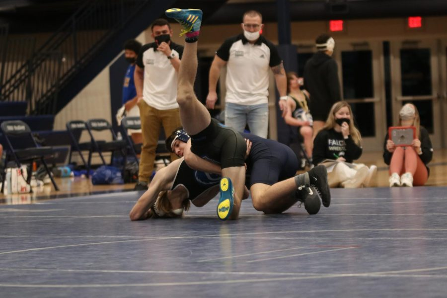 Wrapping around his opponent, senior Nick Whisler pulls him down to the mat.