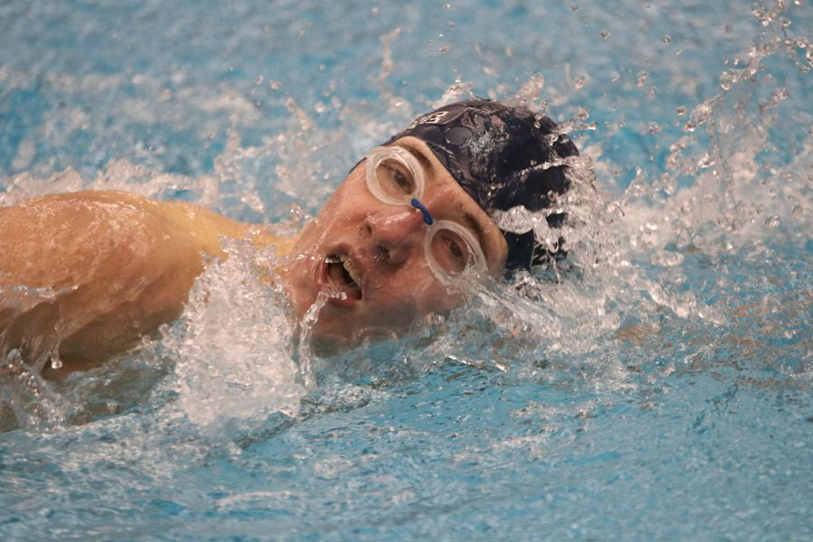 Taking a breath, junior Brendan Akehurst swims the 100-yard freestyle, finishing with a time of 1:18.50.