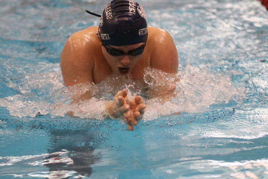 Coming up for air, senior Noah Collins swims the breaststroke portion of the 200-yard individual medley.