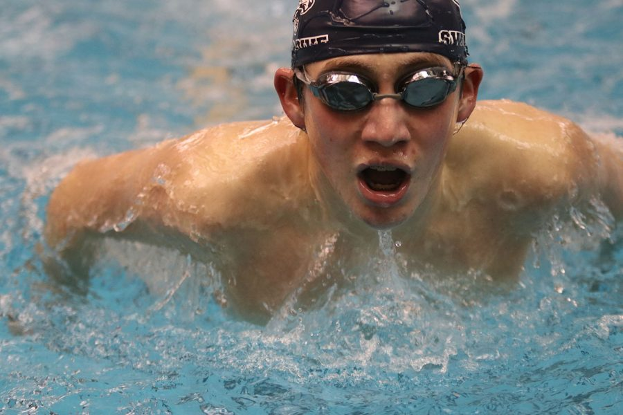 Arms extended, freshman Andre Arnold competes in the 100-yard butterfly with a time of 1:16.94.