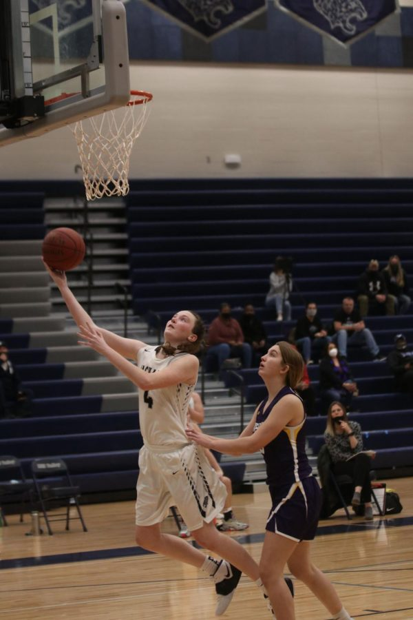 After having been passed the ball, junior Maddie Vosburg shoots a layup.
