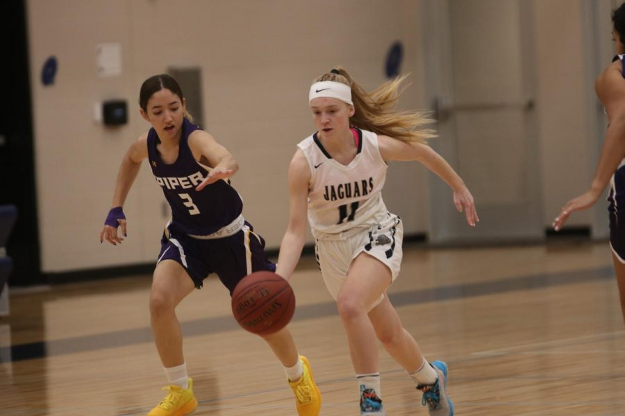 Running past two Piper players, sophomore Sophie Pringle dribbles the ball down the court.