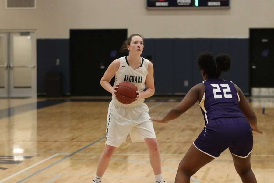Looking for a shot to score, junior Maddie Vosburg takes her time to set up her stance and look for an opportunity to shoot the ball and score.