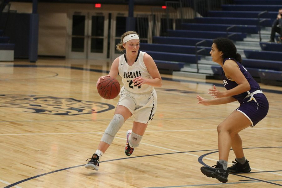 Driving down the court, junior Emree Zars competes against Piper high school Thursday, Jan. 14. The team fell to Piper in the end with a score of 48-25.