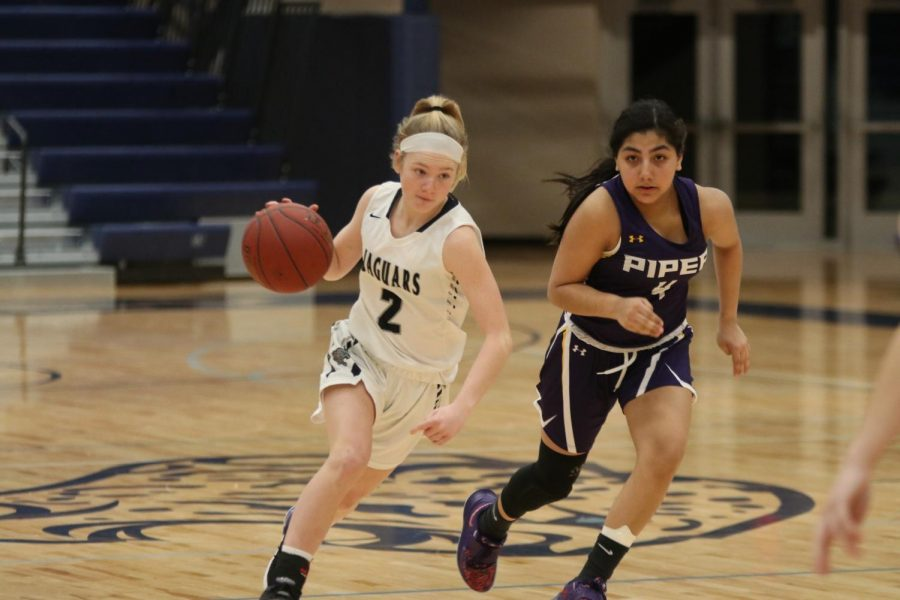 With the ball in her hand, freshman Keira Franken pushes past the defense to dribble the ball down the court.