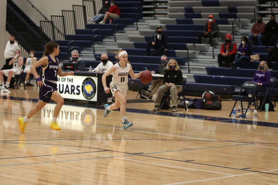 Eyes on the ball, sophomore Sophie Pringle runs down the court to score.