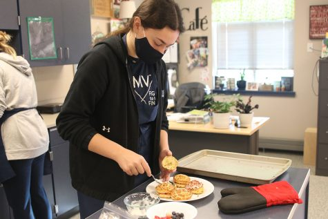 With cinnamon rolls, fruit and icing, senior Carlie Bradshaw finishes plating her dish.