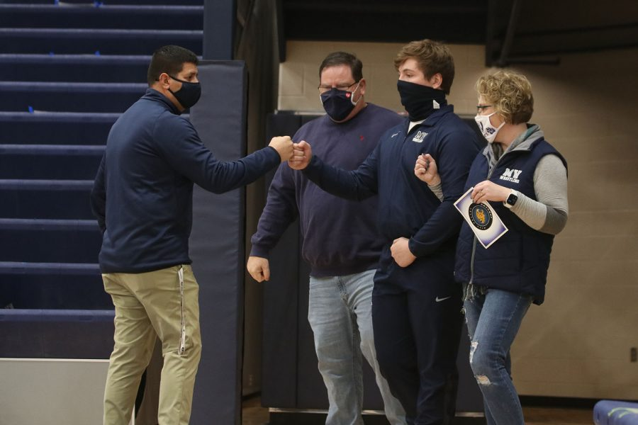 In between his parents, senior Ethan Kremer greets head wrestling coach Travis Keal before walking out.