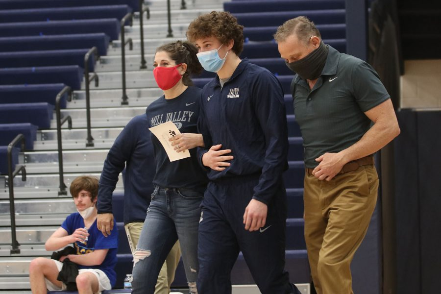 Eyes up, senior Brodie Scott walks alongside his parents to the mat.