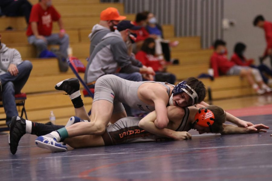 Moving on top, freshman Dillon Cooper works to pin his opponent.