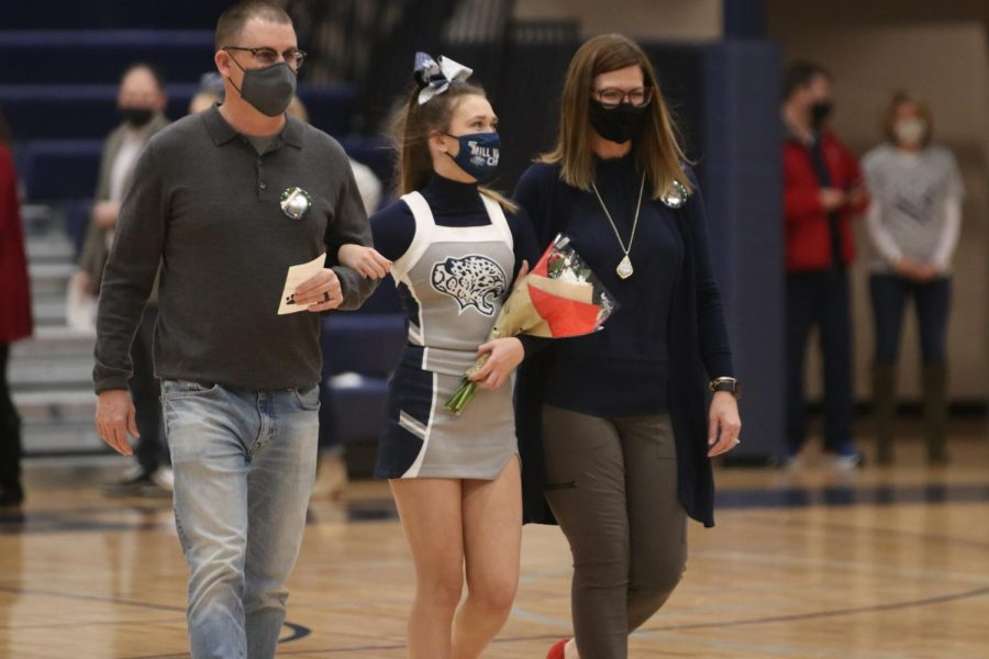 Flowers in her hand, senior Maddy McDonald walks onto the court.