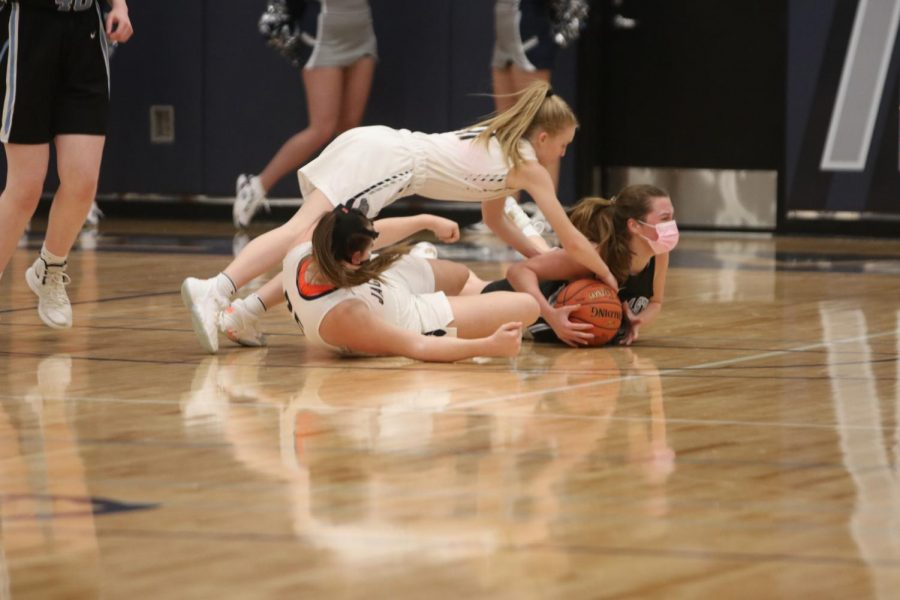 Stretching over her teammate, sophomore Sophie Pringle goes for a jump ball.