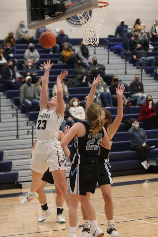 Jumping above three Shawnee Mission East players, senior Elle Zars shoots the ball.