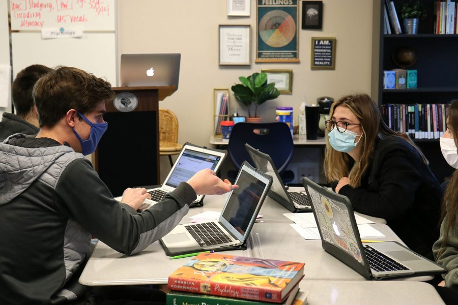 Talking with one another, seniors Kendall France and Alex Conan discuss their answers in newlygroup tables during AP Psychology Friday, Feb. 19.
